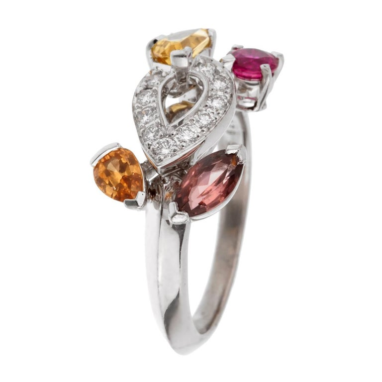 A fabulous Cartier crafted in 18k white gold adorned withwith diamond, ruby, tourmaline, citrine and imperial topaz stones. The ring showcases a knife edge design and measures a size 6 1/2 (Resizeable)