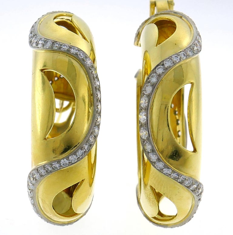 Chic and wearable stylized hoop earrings that are a great addition to your jewelry collection.  Created by Cartier in London.  Made of 18 karat (tested) yellow gold and set with round brilliant cut diamonds (F-G color, VS1 clarity, total weight