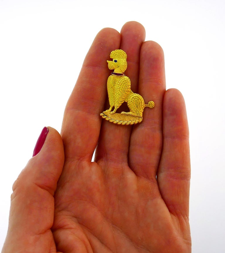 An iconic poodle pin created by Cartier in the 1950s. Cute and joyful, the pin is a great addition to your jewelry collection. The pin is made of 18 karat (stamped) yellow gold, the poodle's collar is encrusted with pre-cut rubies and its eye is