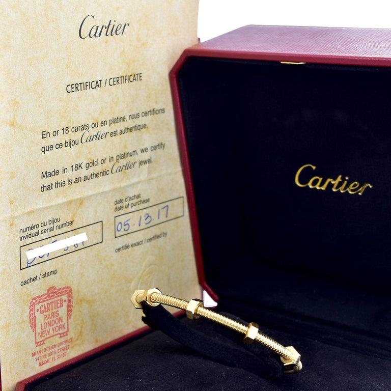 Designer: Cartier  Collection: Ecrou  Style: Bracelet/ Bangle  Metal: Yellow Gold  Metal Purity: 18k  Total Item  Weight ( Grams) : 29.5  Bracelet Size : 18 = 18 Cm  Bracelet Width: 3.5 mm  Hallmarks: Cartier; Serial #; 750  Includes:  24 Months