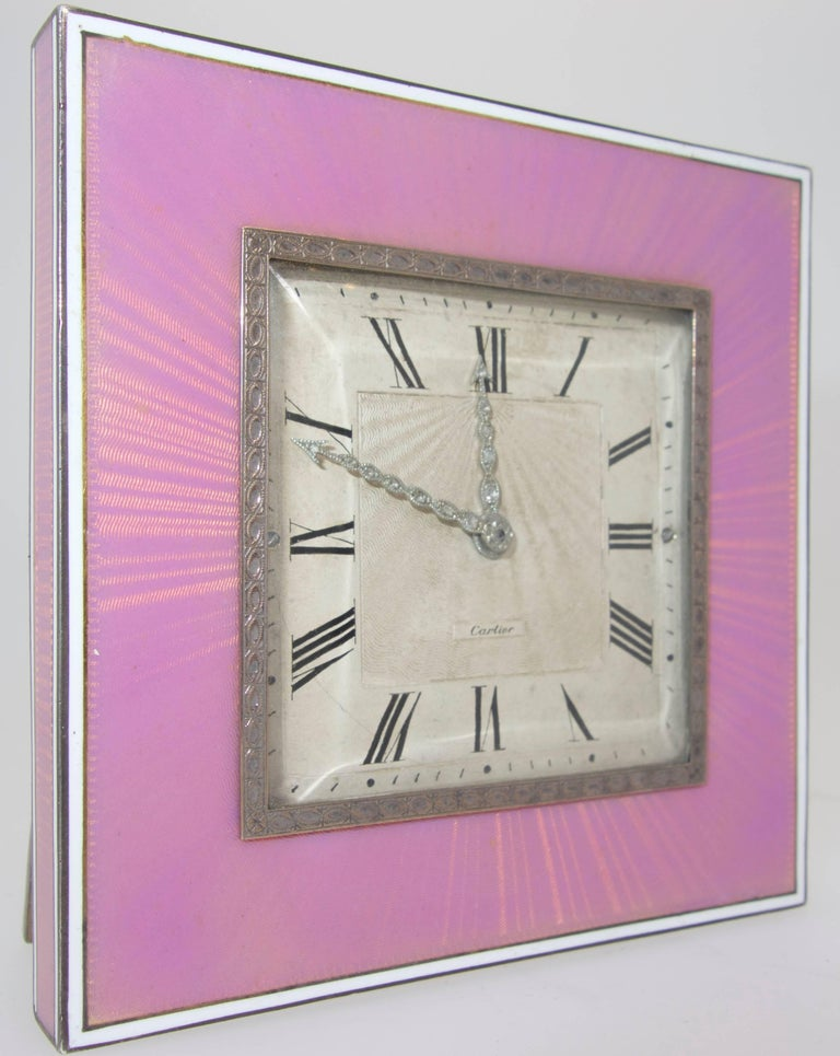 Bright pink guilloche enamel bordered with white opaque enamel, with an original dial,  rose-diamond hands and is signed Cartier above the six position.  The movement is Movado and has recently been serviced and works well.  This clock measures