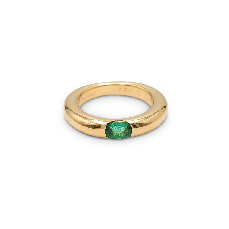 Authentic Cartier 'Ellipse' ring crafted in 18 karat yellow gold and set with one emerald stone weighing an estimated 0.35 carats total weight. Signed Cartier 1992, 750, 50, with serial number. The ring is presented with the original box and papers.