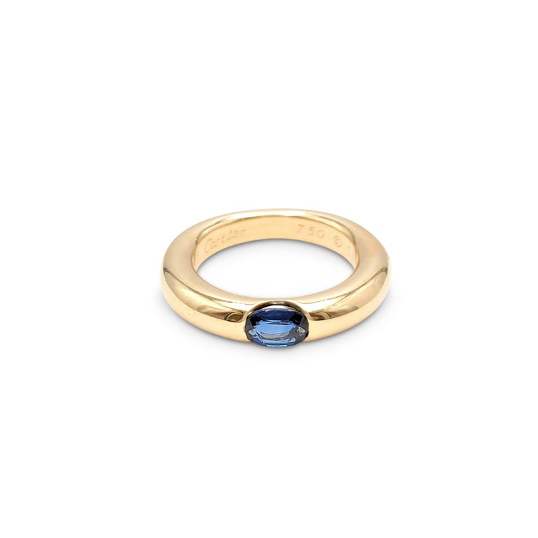Authentic Cartier 'Ellipse' ring crafted in 18 karat yellow gold and set with one blue sapphire weighing an estimated 0.35 carats total weight. Signed Cartier 1992, 750, 49, with serial number. The ring is presented with the original papers, no box.