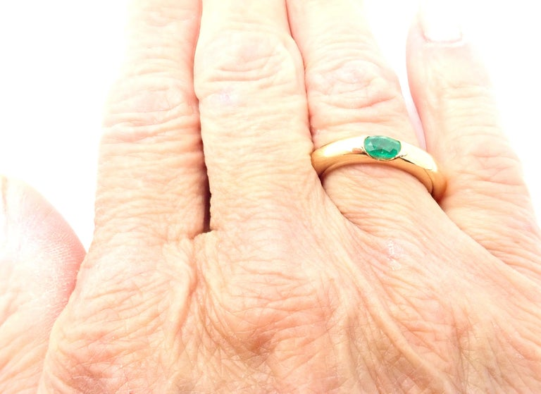 18k Yellow Gold Ellipse Emerald Band Ring by Cartier. With 1 oval-shaped beautiful emerald 5mm x 4mm. Details: Width: 4mm Weight: 9.7 grams Ring Size: European 52, US 6 Stamped Hallmarks: Cartier 750 52 1992 F8XXX(serial number omitted) *Free