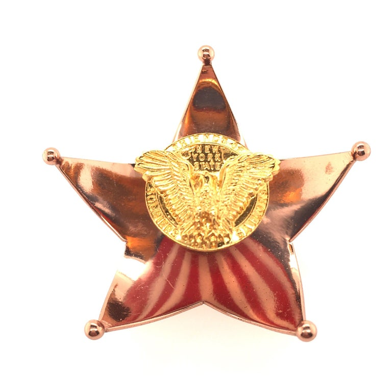 A gilt metal and enamel Stars and Stripes brooch, Cartier, circa 1940. Designed as a copper colored curving star, centering a flared en tremblant segment applied with red, white and blue enamel in an American flag motif, surmounted by an emblem of