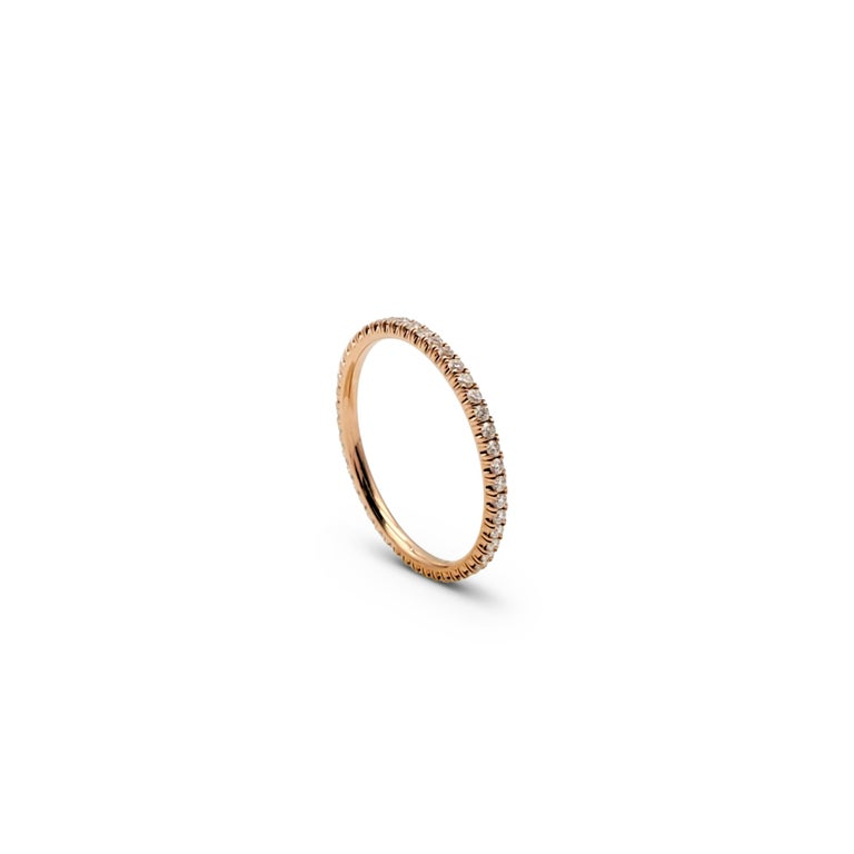 Authentic Cartier 'Étincelle de Cartier' wedding band crafted in 18 karat rose gold, set with round brilliant cut diamonds (E-F, VS) totaling 0.22 carats. Signed Cartier, 50, Au750, with serial number. Ring size 50 (US 5 1/4). The ring is presented