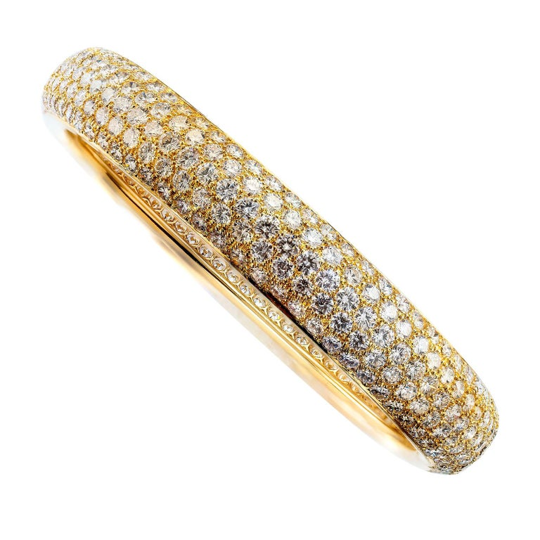 "Cartier ""Etincelle"" wide diamond pavé yellow gold bangle bracelet.   DETAILS: DIAMONDS:  three hundred seventy round brilliant-cut diamonds all the way around totaling approximately 18.41 carats, approximately E – F color, VS-VVS clarity.  METAL:"
