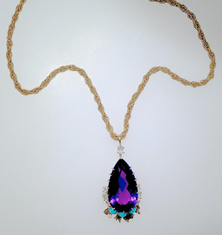 Cartier has set a very fine natural Siberian amethyst as a tear drop, accented with rose cut diamonds and Persian Turquoise from a Cartier 18K gold chain.  This center stone which has wonderful flashes of red - a hallmark of fine amethysts from