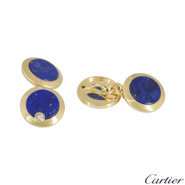 A pair of 18k yellow gold lazuli cufflinks by Cartier. The cufflinks feature 2 discs attached together by a chain set to the centre with blue lapis lazuli with a single round brilliant cut diamond and yellow gold border. The cufflinks have a