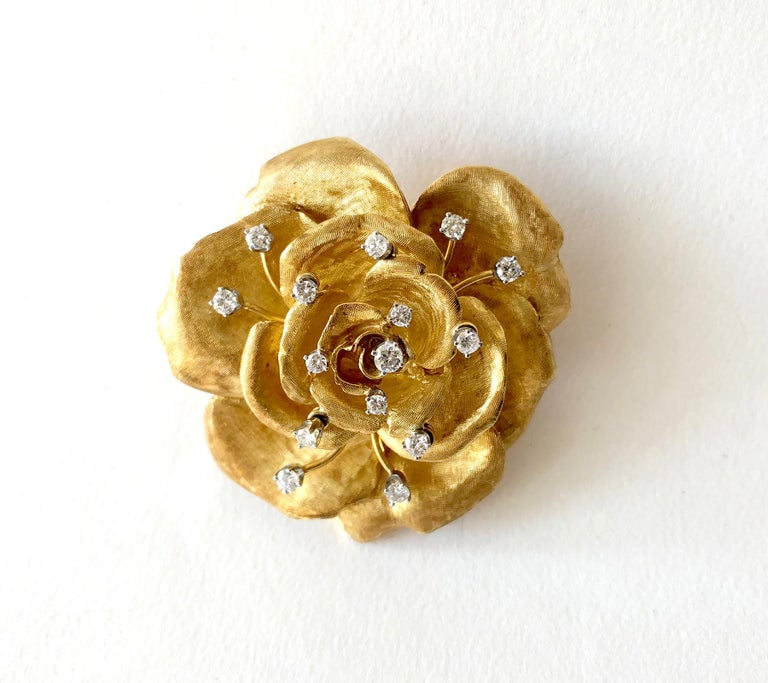An 18 karat gold and diamond rose flower brooch and matching earrings created by Cartier of France. The set has a Florentine finish to the petals with 15 full cut diamonds in the brooch, some of them en tremblant. The earrings have one single