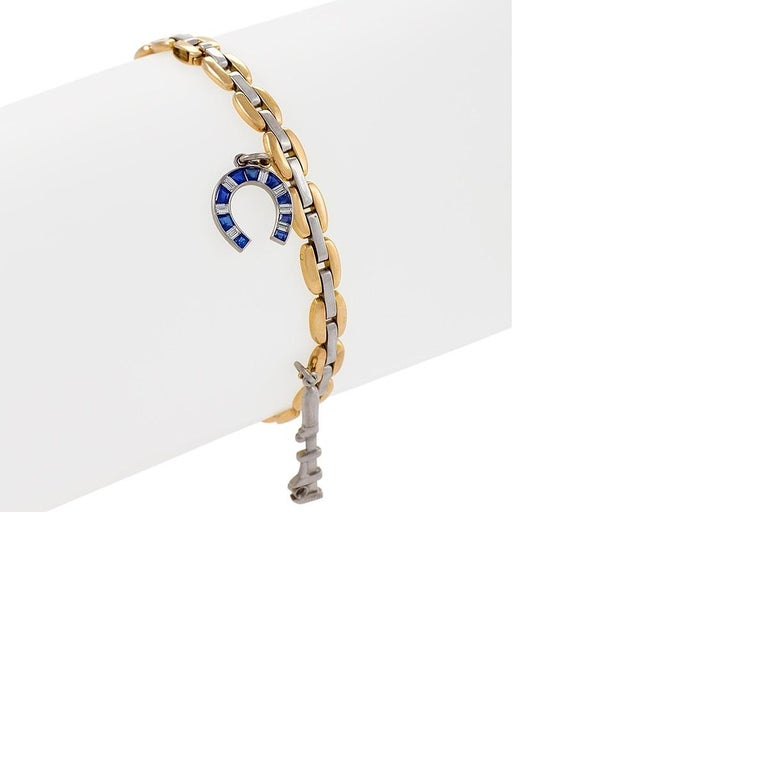 A two tone bracelet in platinum and 18k yellow gold with charms by Cartier. The bracelet has five charms, a sapphire and diamond horseshoe, a diamond accented wrench, a pair of fully articulated scissors, a house with emerald and sapphire accents