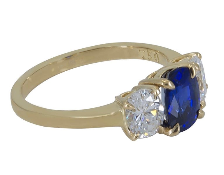 Exceptional handmade Cartier Sapphire and Diamond 18K Yellow Gold Ring.  The exquisite Oval Blue Sapphire is 1.71 carats, accompanied by a GIA (Gemological Institute of America) report.  It is accentuated by two matched Oval Cut Diamonds that weigh