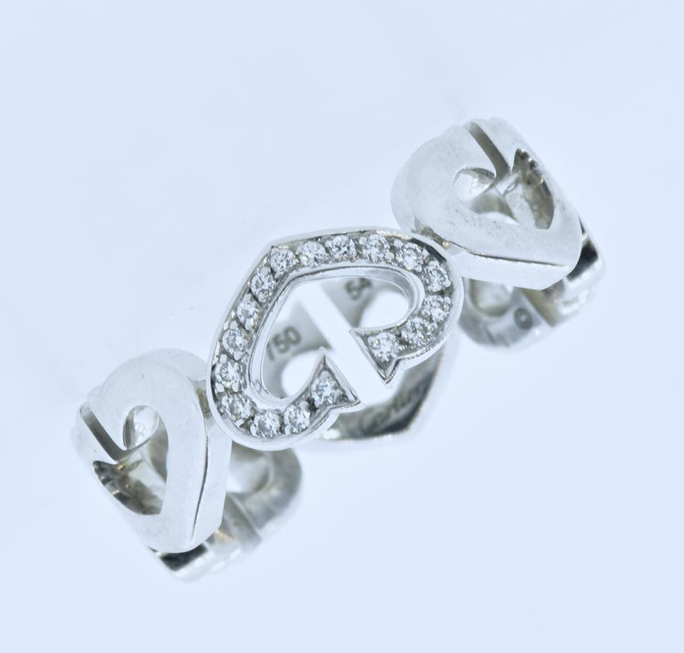 Cartier diamond and 18K gold band ring.  Hearts and Symbols contemporary line with approximately .10 cts of white brilliant cut diamonds - near colorless (F/G), and very slightly included (VS1).  This ring is signed, numbered with its size which is