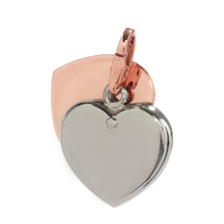 A lovely heart charm pendant by Cartier featuring 18k white and rose gold, forming a perfect colorful combination.