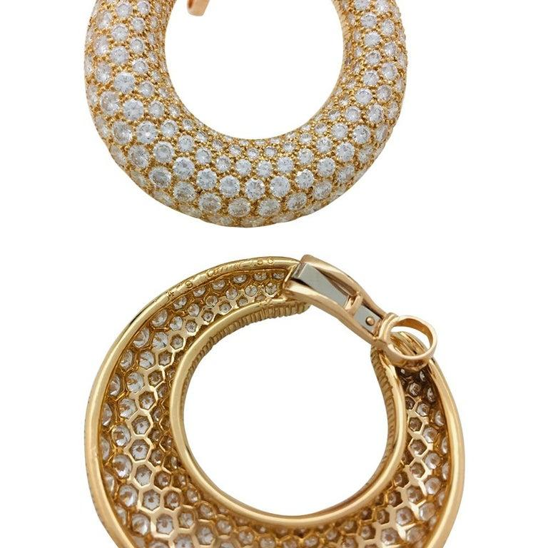 A 750/000 yellow gold, Cartier pair of earrings, hoop style, entirely paved with brilliant cut diamonds.Clip system. Total weight of diamonds : about 13 carats Cartier signed and numbered, french mark. Circa 1995