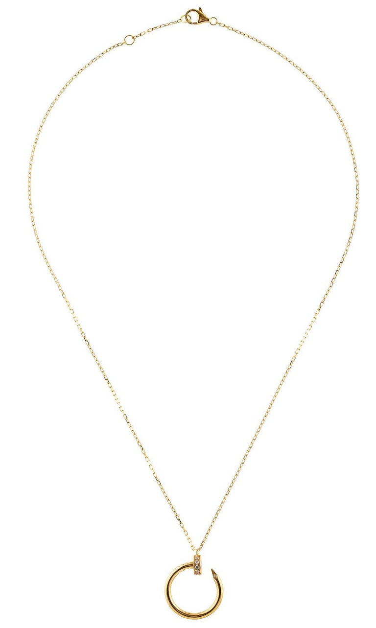 An authentic Cartier Juste un Clou necklace made in 18K yellow gold, set with 14 brilliant-cut diamonds totaling 0.12 carats. This necklace is 16 inches long. The nail pendant is .75 inches in diameter. The clasp is hallmarked Cartier AU750. Bid