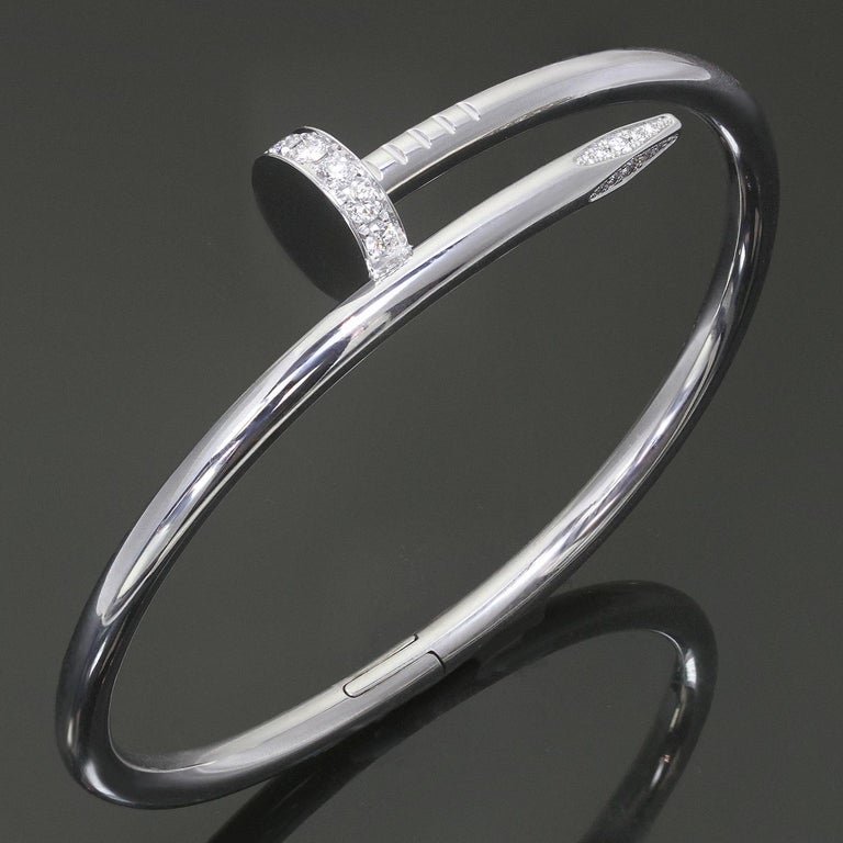 This chic hinged bangle from Cartier's Juste Un Clou collection is crafted in 18 white gold and pave-set with round brilliant D-F VVS1-VVS2 diamonds weighing an estimated 0.59 carats. This bracelet is a size 16. Made in United States circa 2010s.
