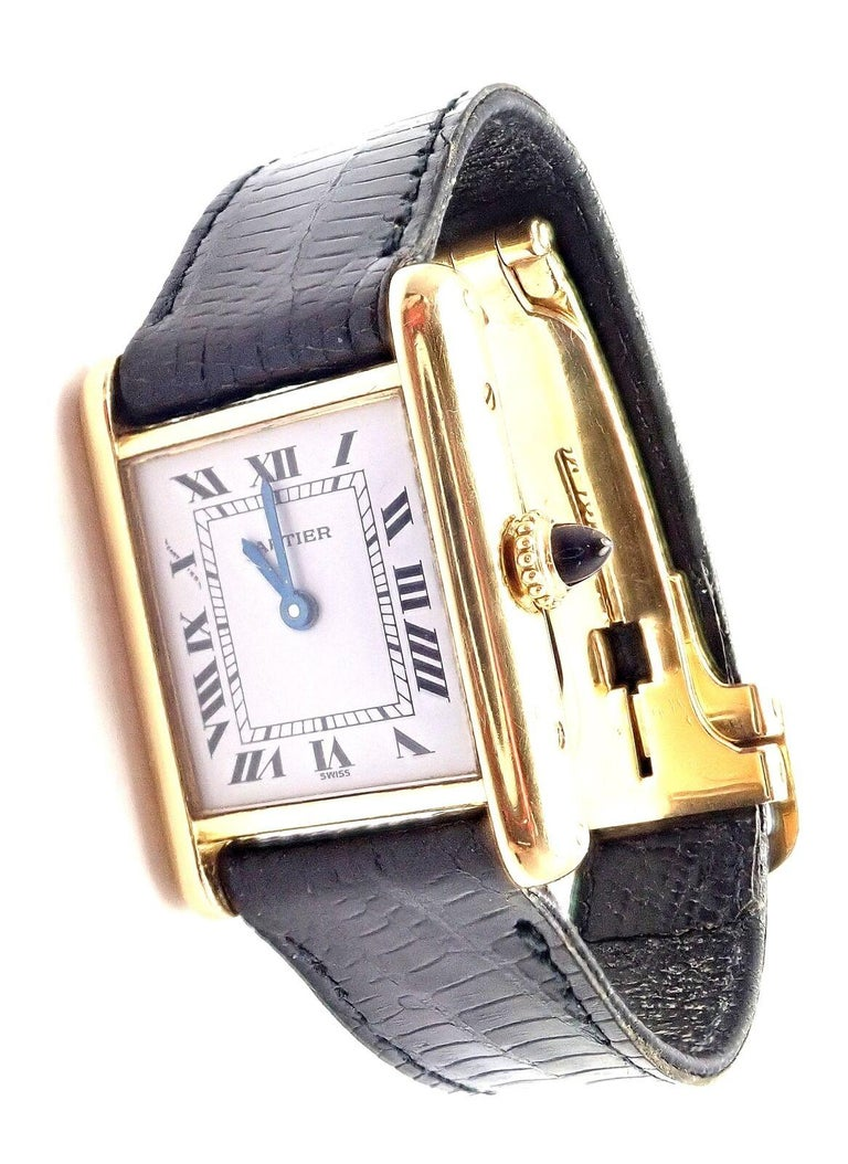 Lady's 18k yellow gold Cartier Tank wristwatch. Details:  Brand: Cartier Case Material: 18k Yellow Gold Dial Color: White Movement: Manual Wind Functions: Hours, Minutes Crystal: Cartier mineral glass crystal Case: 28mm x 21mm Crown: Sapphire Strap: