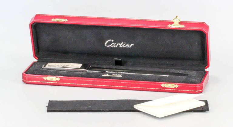 Handsome limited edition (#1068 of 2000 made) clock/letter opener by Cartier. It features a large clock at the end of it, with a quartz movement and roman numerals. Comes with original Cartier box and papers. Beautifully made and would make a great