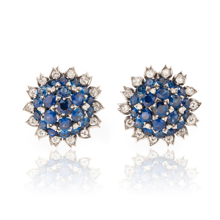 This exceptionally rare 1960s sapphire and diamond suite from Cartier London is composed of a brooch and ear clips designed as stylized flowers. The sapphires gradually slope upwards to the center, giving the pieces a substantial three-dimensional