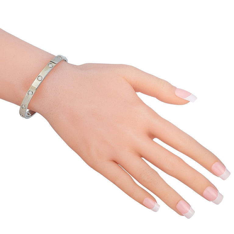 """The Cartier """"LOVE"""" bracelet is crafted from 18K white gold and set with 10 diamond stones that amount to 0.96 carats. The bracelet weighs 33.1 grams, measures 7.40"""" in length.  This jewelry piece is offered in estate condition and includes a gift"""