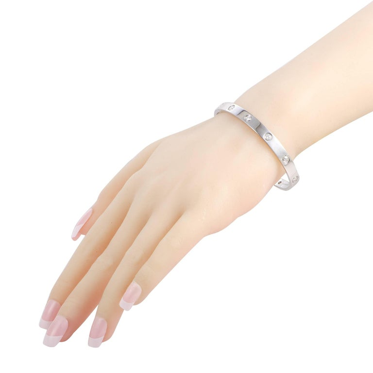 """A piece from the acclaimed """"LOVE"""" collection by Cartier, this sublime bracelet offers a splendidly elegant look. The bracelet is made of 18K white gold and it is set with 10 diamonds that amount to 0.96 carats. This bracelet comes with a matching"""
