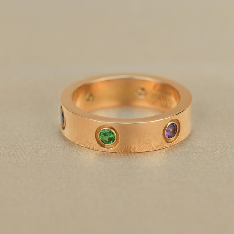 LOVE ring, 18K rose gold, set with 1 pink sapphire, 1 blue sapphire, 1 yellow sapphire, 1 green garnet, 1 orange garnet, and 1 amethyst. Width: 5.5mm.  Dandelion Antiques CodeAT-0833 Brand                                Cartier Model