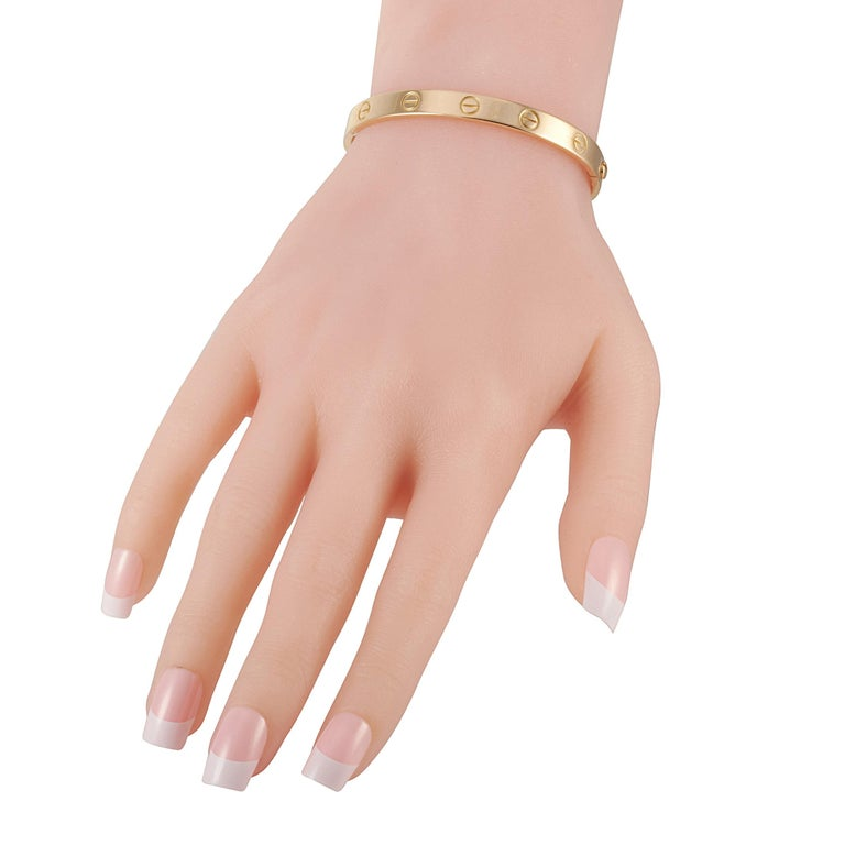 """The Cartier """"LOVE"""" bracelet is crafted from 18K yellow gold and measures 6.3"""" in length. The bracelet weighs 28.5 grams and is delivered with a screwdriver.  This jewelry piece is offered in estate condition and includes a gift box."""