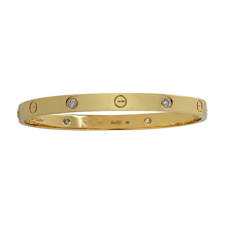 Cartier LOVE bracelet crafted in 18 Karat Yellow Gold, featuring 4 round brilliant cut diamonds weighing approximately .40 carats total. The Cartier love collection is a timeless tribute to the symbol of love that transcends through the decades in
