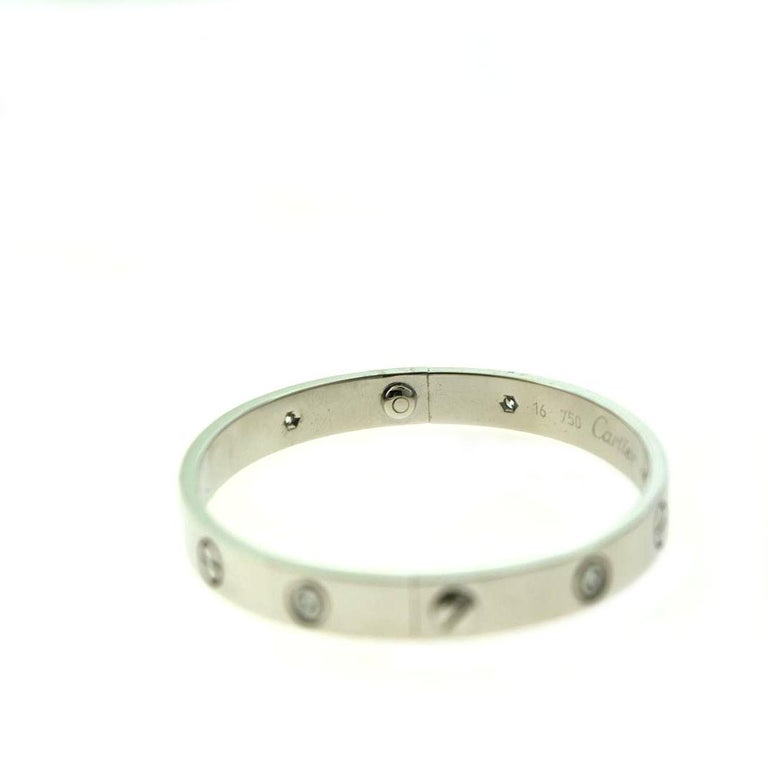 Designer: Cartier  Collection: Love  Style: Bangle Bracelet  Metal: White Gold  Metal Purity: 18k  Bracelet Size: 16 = 16 cm  Stones: 6 Round Brilliant Cut Diamonds  Hallmarks: 16, Au750 Cartier, Serial No.,  Screw System: