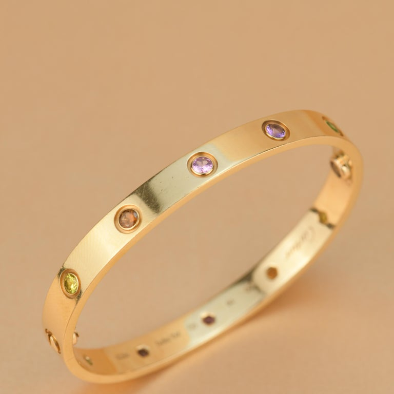 LOVE bracelet, 18K rose gold, set with 2 pink sapphires, 2 yellow sapphires, 2 green garnets, 2 orange garnets, and 2 amethysts.  Comes with Cartier Box / Authentic card. Size 16 __________________________________  Dandelion Antiques Code