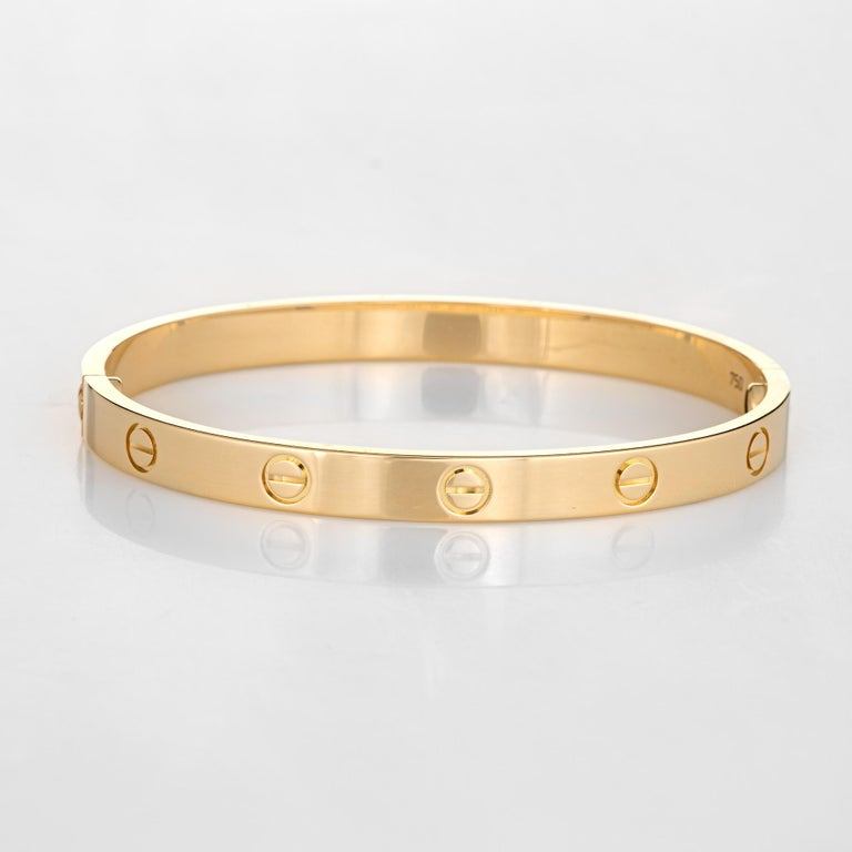 Pre owned Cartier love bracelet crafted in 18 karat yellow gold.    The bracelet is a size 18 and features the new screw system (easier to screw on and off compared to older model Cartier love bracelets).  The bracelet is in excellent condition and