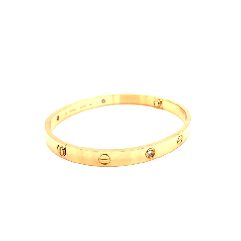 Gorgeous and timeless design. The Cartier love bracelet is an iconic bracelet. Crafted in 18K yellow gold,  size 20 set with 4 brilliant-cut diamonds totaling 0.42 carats. This item comes with original box, key and Cartier certification paperwork.