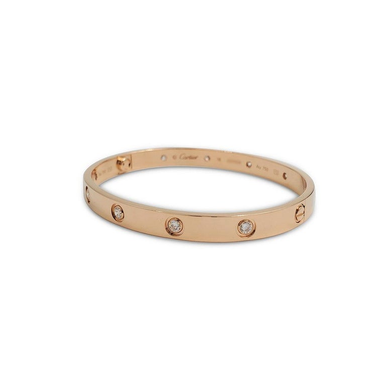 Authentic Cartier 'Love' bangle bracelet crafted in 18 karat rose gold set with ten round brilliant cut diamonds (E-F in color, VS clarity) weighing an estimated 0.96 carats total. Signed Cartier, size 18, Au750, with serial number. The bracelet is
