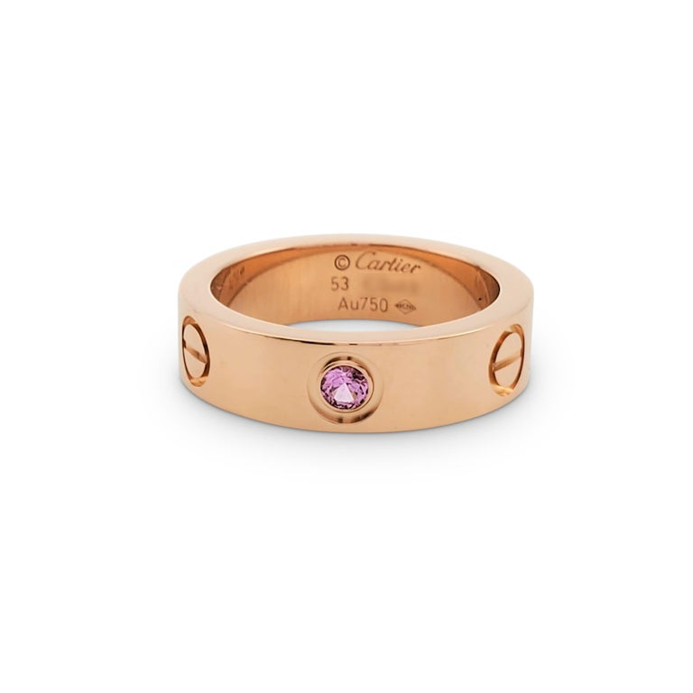 Authentic Cartier 'Love' ring crafted in 18 karat rose gold and set with one round pink sapphire weighing an estimated 0.06 carats. Signed Cartier, 53, Au750, with serial number. Ring size 53 (US 6 1/4). The ring is presented with the original box