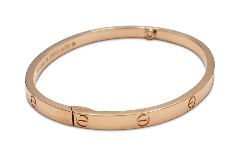 Authentic Cartier 'Love' bracelet crafted in 18 karat rose gold. Size 16. Signed Cartier, Au750, with serial numbers. The bracelet is presented with the original screwdriver, Cartier papers, and box. CIRCA 2010s.