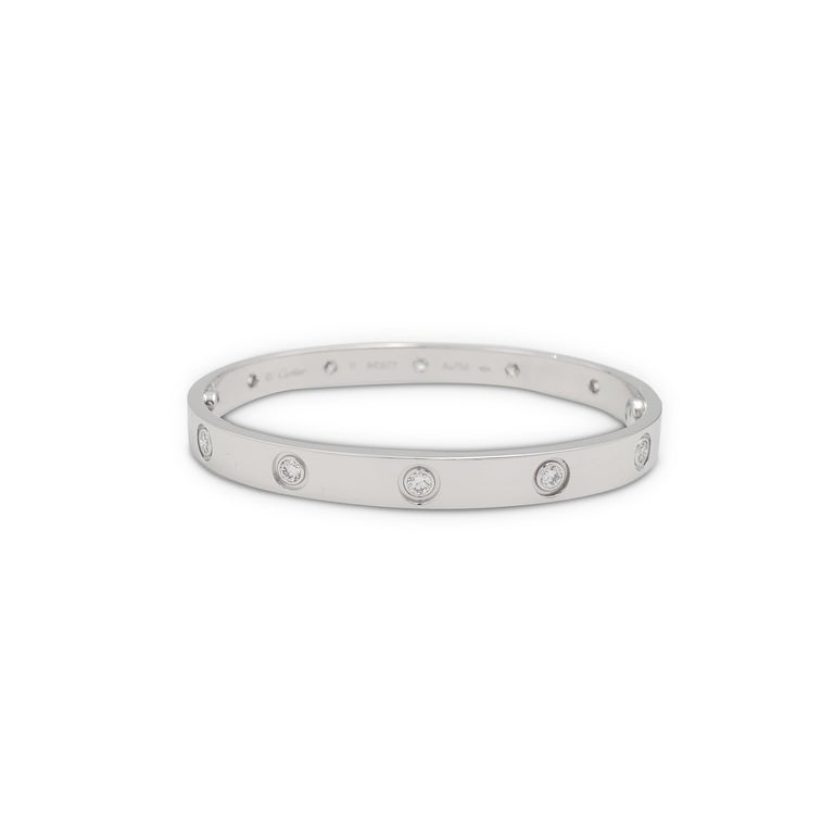 Authentic Cartier 'Love' bracelet crafted in 18 karat white gold is set with ten round brilliant cut diamonds (E-F, VS) weighing 0.96 carats total. Signed Cartier, Au750, 17, with serial number. The bracelet is presented with the original papers,