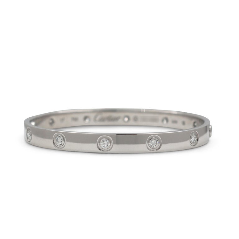 Authentic Cartier 'Love' bracelet crafted in 18 karat white gold and set with ten high-quality round brilliant cut diamonds E-F in color, VS clarity) weighing an estimated 0.96 carats total. Size 17. Signed Cartier, 750, 17, with serial number and