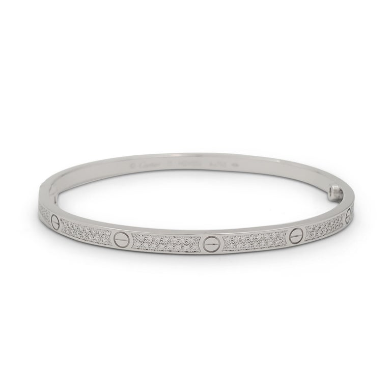 Authentic Cartier 'Love' bracelet crafted in 18 karat white gold and pavé set with an estimated 0.95 carats of round brilliant cut diamonds (E-F, VS). Signed Cartier, Au750, 17, with serial number. The bracelet is presented with the original Cartier