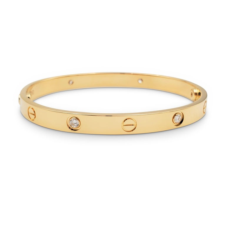 Authentic Cartier 'Love' bracelet crafted in 18 karat yellow gold and set with four high-quality round brilliant cut diamonds (E-F color, VS clarity) weighing an estimated 0.42 carats total. Size 18. Signed Cartier, 750, 18, with serial number and