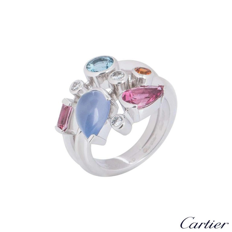 A platinum Cartier diamond and multi-gemstone ring from the Meli Melo collection. The ring comprises of 8 gemstones abstractly placed over 3 rows, consisting of diamonds, aquamarine, chalcedony, garnet and pink tourmaline. There are 3 round