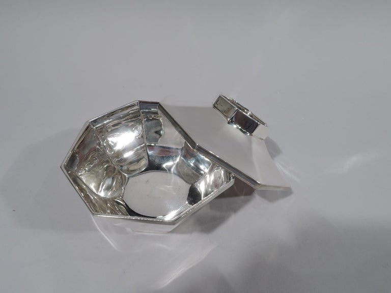 Mid-Century Modern sterling silver bowl. Retailed by Cartier in New York. Curved and faceted sides with flat rim and inset same foot. Cover faceted and overhanging with inset faceted gallery. Stylish geometric form. Fully marked including maker's