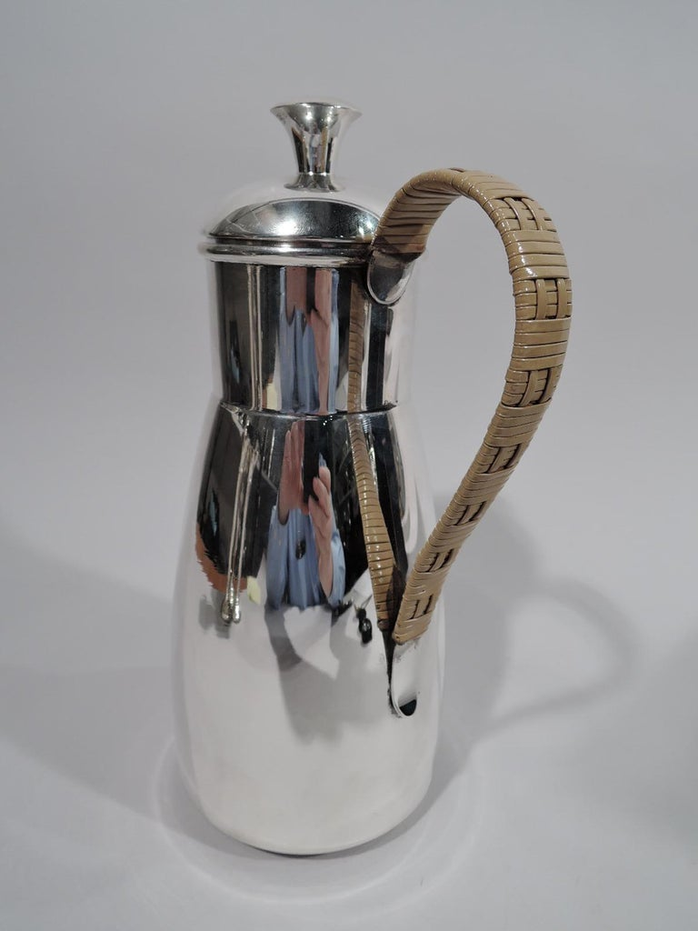 Mid-Century Modern sterling silver martini pitcher. Retailed by Cartier in New York. Truncated cone body, straight drum-form neck, v-spout with built in strainer, and domed cover. Handle scrolled and wrapped in rattan-style weave. Fully marked