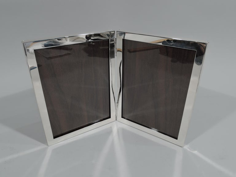 Modern sterling silver diptych picture frame. Two hinged rectangular windows with flat surrounds. With glass and wood laminate back. Fully marked including maker's and retailer's stamps. The maker was Hickok-Matthews, a Newark maker better known by
