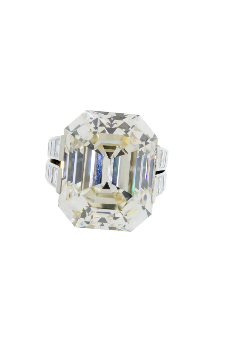 A 30.03 carat L Faint Brown VVS1 GIA certified emerald cut diamond set in an 18 grams of platinum signed by Cartier Monture. The setting features 28 baguette cut diamonds weighing 4.10 carats, and 65 round brilliant stones weighing 1.70 carats. This