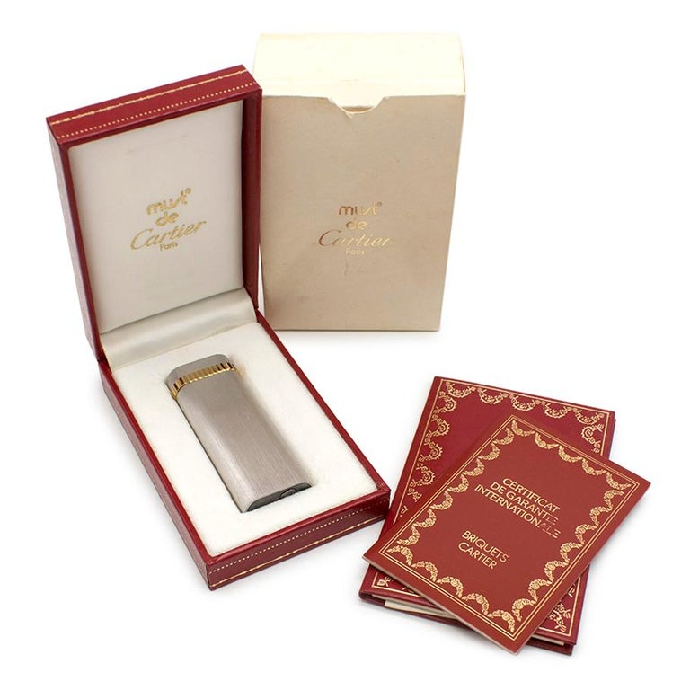 Cartier Must De Cartier Silver Plated Briquet Lighter  Brushed Silver Plated Finish Gold plated trim  Refillable with refill prong and instructions included Cartier Box included Certificate and Care Booklet included  Please note, these items are