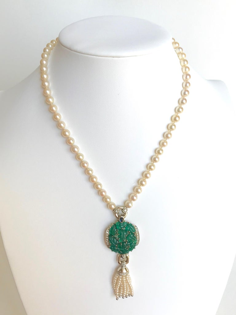 CARTIER Necklace in Pearls and Chrysoprases Pearl Necklace retaining a large white gold pendant, engraved Chrysoprases in the shape of Leaves, Diamonds, Cabochon Sapphire and ending with a beaded Tassel and Pearls of white Gold. Signed CARTIER 1990