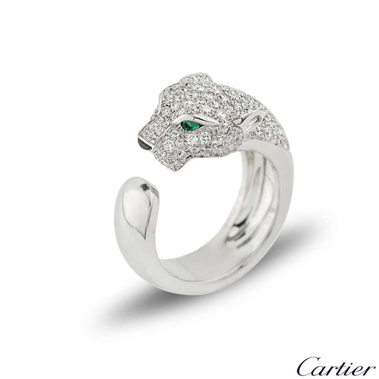 A stunning 18k white gold Cartier diamond, onyx and emerald ring from the Panthere De Cartier collection. The ring is composed of a Panthere head motif, pave set with 137 round brilliant cut diamonds totalling 1.15ct, accentuated by two emeralds set
