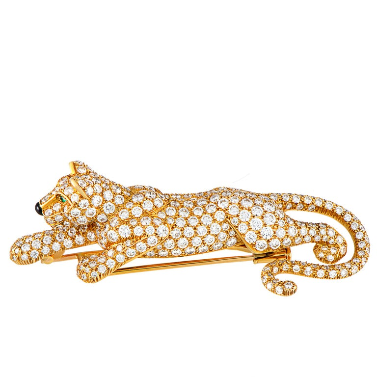 """This vintage """"Panthère"""" brooch by Cartier is crafted from 18K yellow gold and embellished with onyx and emerald stones and a total of approximately 8.00 carats of diamonds that boast grade F color and VS1 clarity. The brooch weighs 25.7 grams and"""