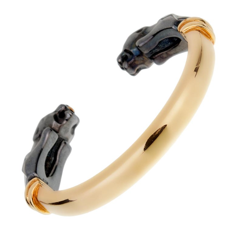 An 18k yellow gold and hematite cuff bracelet from the Panthere de Cartier collection. The bracelet is composed of 2 hematite Panther heads facing each other with 18k yellow gold eyes.